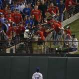 Texas Rangers left fielder Josh Hamilton watches as fans try to catch Buster Posey's eighth inning home run in Game 4 of the World Series on Sunday.