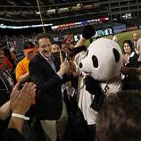 San Francisco Giants president Larry Baer (left of Panda) and San Francisco Giants managing general partner William Neukom (right) celebrate with fans after Game 4 of the World Series at Rangers Ballpark on Sunday.