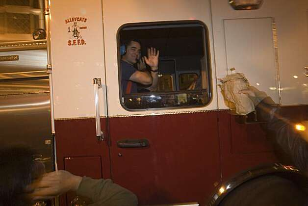 A San Francisco firefighter waves to Giants fans celebrating  the World Series win at the intersection of 5th Street and Market in San Francisco, Calif., on Monday, November 1, 2010. Photo: Douglas Zimmerman, Courtesy To The SF Gate