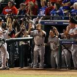 Buster Posey returns to the dugout after hitting a solo home run in the eighth inning of Game 4 of the World Series at Rangers Ballpark on Sunday.