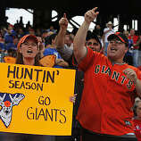 Lisa Lobrano of San Jose, left, and Avi Kushlan of Palo Alto cheer for the Giants during a workout before Game 4 of the World Series on Sunday.