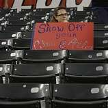 Thresa Belcher of Flower Mound, Texas, sits with her sign as people leave Rangers Ballpark after Game 4 of the World Series on Sunday.