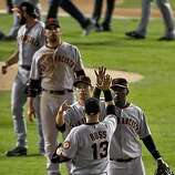 Freddy Sanchez and Edgar Renteria high five Cody Ross after the Giants defeated the Rangers 4-0, to take a 3 games to 1 lead in the World Series. The San Francisco Giants played the Texas Rangers at Rangers Ballpark in Arlington, Tx, in Game 4 of the World Series on Sunday, October 31, 2010.