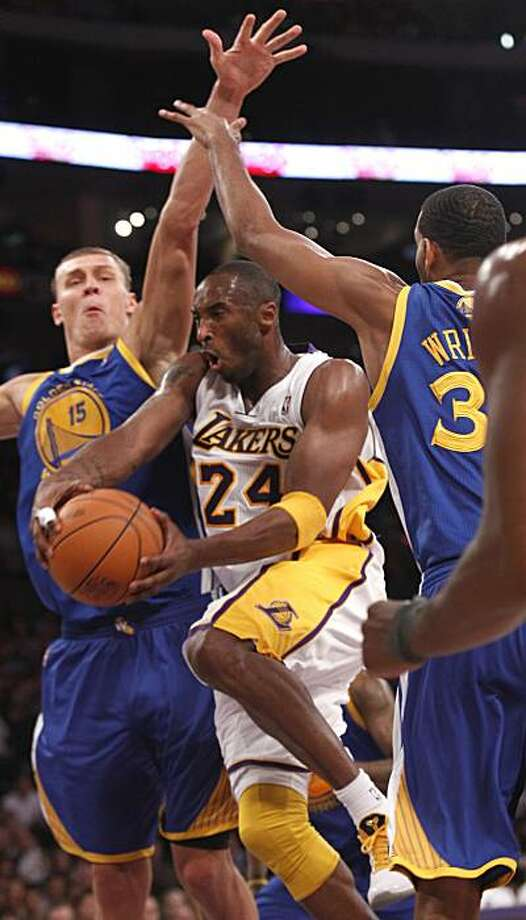 Los Angeles Lakers shooting guard Kobe Bryant (24) passes the ball through Golden State Warriors center Andris Biedrins (15) and  forward Brandan Wright , right, during the first half of an NBA basketball game in Los Angeles , Sunday, Oct. 31, 2010. Photo: Lori Shepler, AP