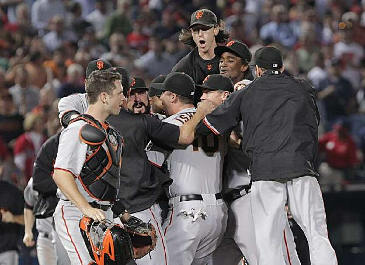 Members of the San Francisco Giants, including Tim Lincecum, top, react at the end of a 3-2 win over the Atlanta Braves in Game 4 of baseball's National League Division Series on Monday, Oct. 11, 2010, in Atlanta.