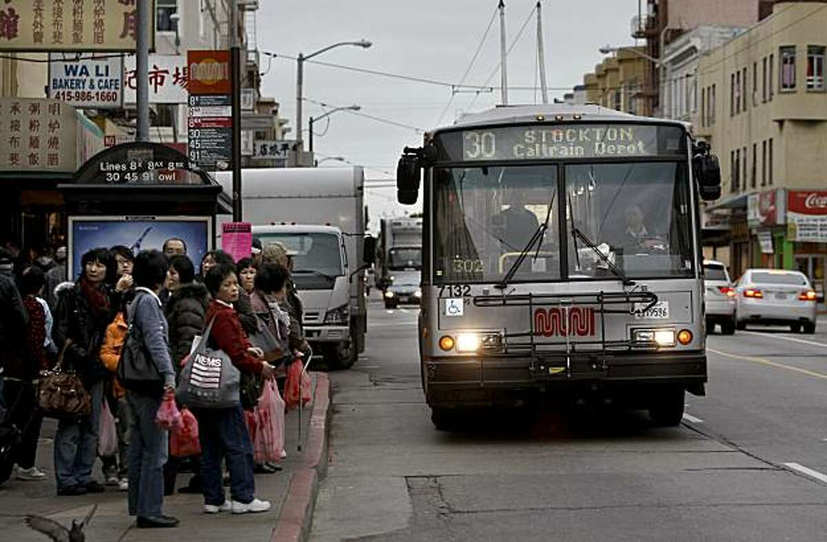 A Muni bus prepares to pick up passengers along Stockton Street near Broadway on Friday.