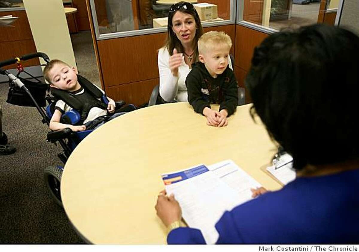 Austin Rustrum, who is wheelchair bound and has cerebral palsy looks on as Chase banker Cynthia Thompson (right) goes over financial information of his mother Stacey Rustrum (holding her other son Wyatt Rustrum) at Chase's Homeownership Center in Oakland, Calif. on Tuesday, March 17, 2009.