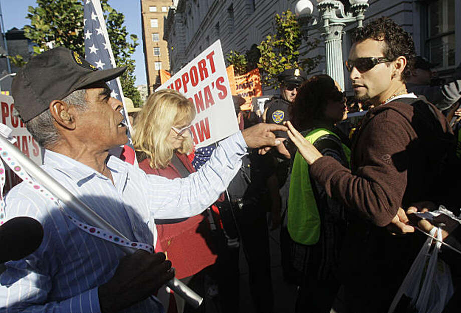 Raymond Herrera, a supporter of Arizona's new immigration law, left, argues with Gerardo Marin outside of a U.S. Circuit Court of Appeals building in San Francisco, Monday, Nov. 1, 2010. A federal appeals court is hearing arguments over Arizona's requestto enforce its controversial new immigration law. Photo: Jeff Chiu, AP