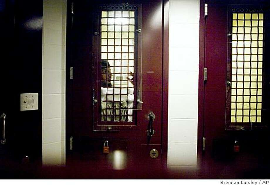 In this image reviewed by the U.S. Military, a Guantanamo detainee stands inside a holding cell, photographed through a glass wall, at Camp 5 detention facility, at the U.S. Naval Base, in Guantanamo Bay, Cuba, Nov. 19, 2008. A former Bush administration official said Thursday, March 19, 2009 that many detainees locked up at Guantanamo were innocent men swept up by U.S. forces unable to distinguish enemies from noncombatants. (AP Photo/Brennan Linsley) Photo: Brennan Linsley, AP