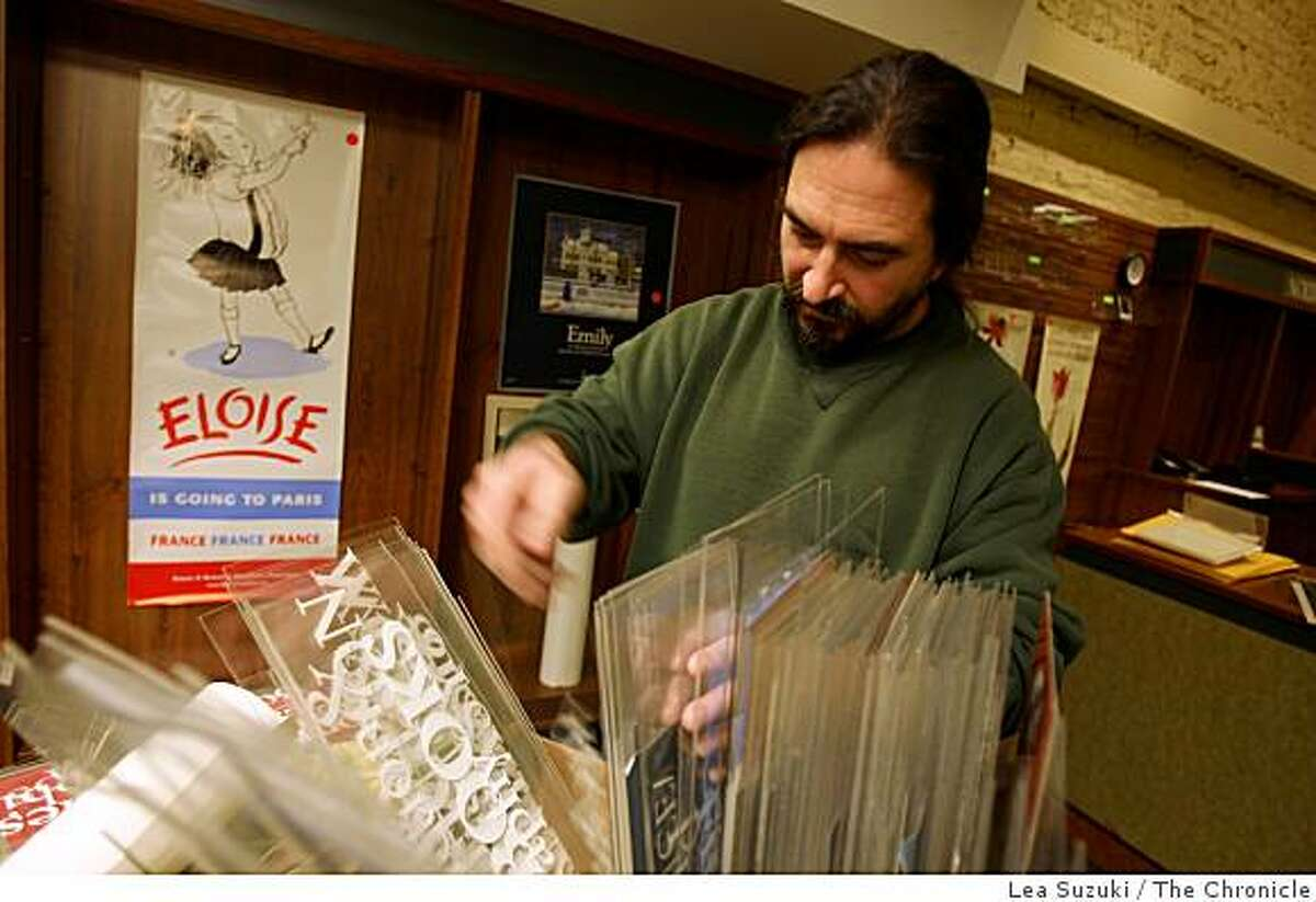 Rob Black of Sunnyvale looks through a box of signs up for sale that were used in Stacey's Bookstore in San Francisco, Calif. on Tuesday, March 17, 2009.