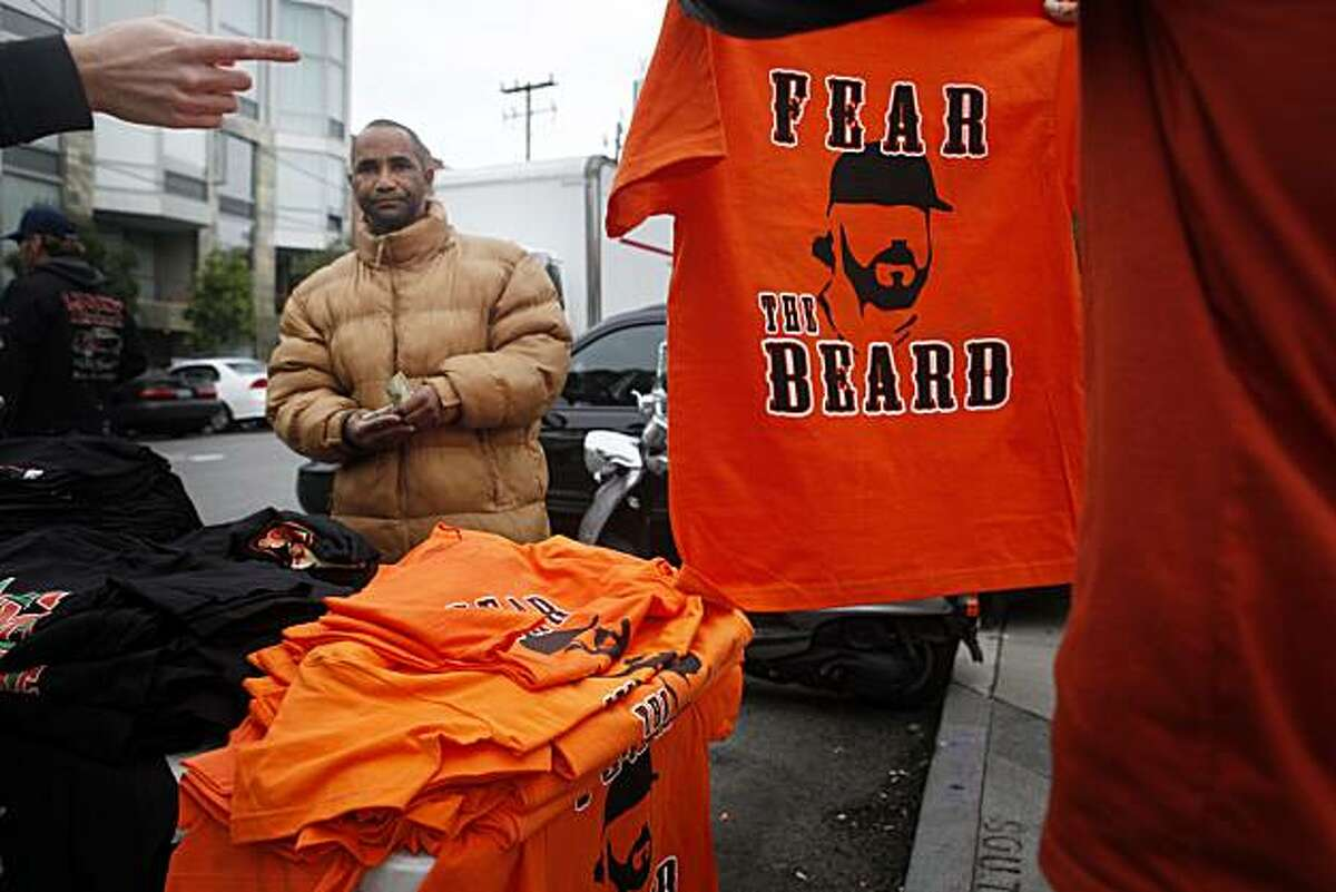 Fans debate a purchase on 3rd Street where Billy Scott sells unofficial t-shirts for $15 dollars near ATT&T Park before the start of Game 1 on the World Series with the San Francisco Giants and Texas Rangers on Tuesday Oct. 27, 2010 in San Francisco, Calif.