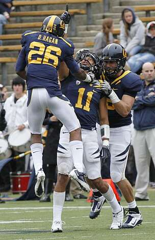 California's Sean Cattouse (11) celebrates with teammates Darian Hagan (26) and Mike Mohamed after making an interception against Arizona State in the first half of an NCAA college football game, Saturday, Oct. 23, 2010 in Berkeley, Calif. Photo: George Nikitin, AP