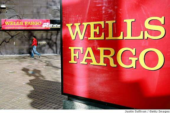 OAKLAND, CA - JANUARY 28:  A pedestrian walks by a sign outside of a Wells Fargo bank branchJanuary 28, 2009 in Oakland, California. San Francisco based Wells Fargo & Co reported a quarterly loss of $2.55 billion, or 79 cents a share, compared to a  profit of $1.36 billion, or 41 cents a share one year ago. The loss comes after Wells Fargo purchased Wachovia Bank late last year and is the first quarterly loss since 2001.  (Photo by Justin Sullivan/Getty Images)