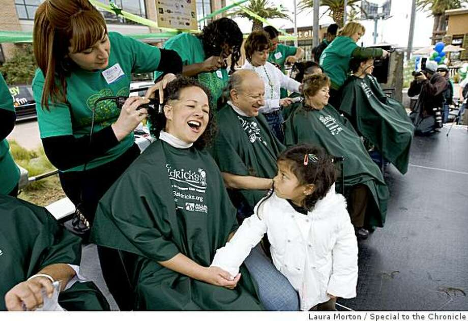 Susy Garcia has her head shaved as her daughter Joecy Garcia, age 4, looks on during the St. Baldrick's Foundation fundraiser in the plaza at Bay Street in Emeryville, Calif., on Saturday, March 14, 2009.  Participants shaved their heads in solidarity of children with cancer, while requesting donations of support from friends and family. Photo: Laura Morton, Special To The Chronicle
