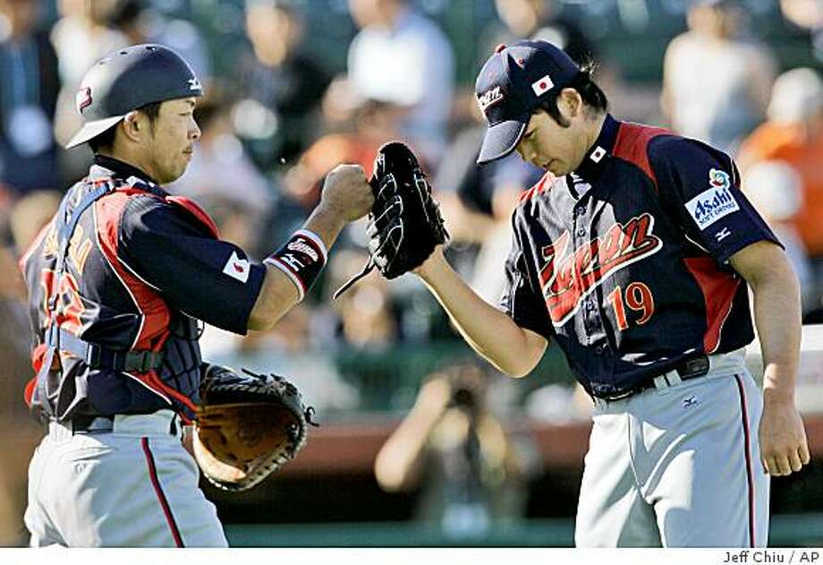 Japan's Yoshiyuki Ishihara, left, celebrates with pitcher Minoru Iwata after defeating the San Francisco Giants in an exhibition spring baseball game in Scottsdale, Ariz., Wednesday, March 11, 2009. Japan won 6-4. (AP Photo/Jeff Chiu) Photo: Jeff Chiu, AP