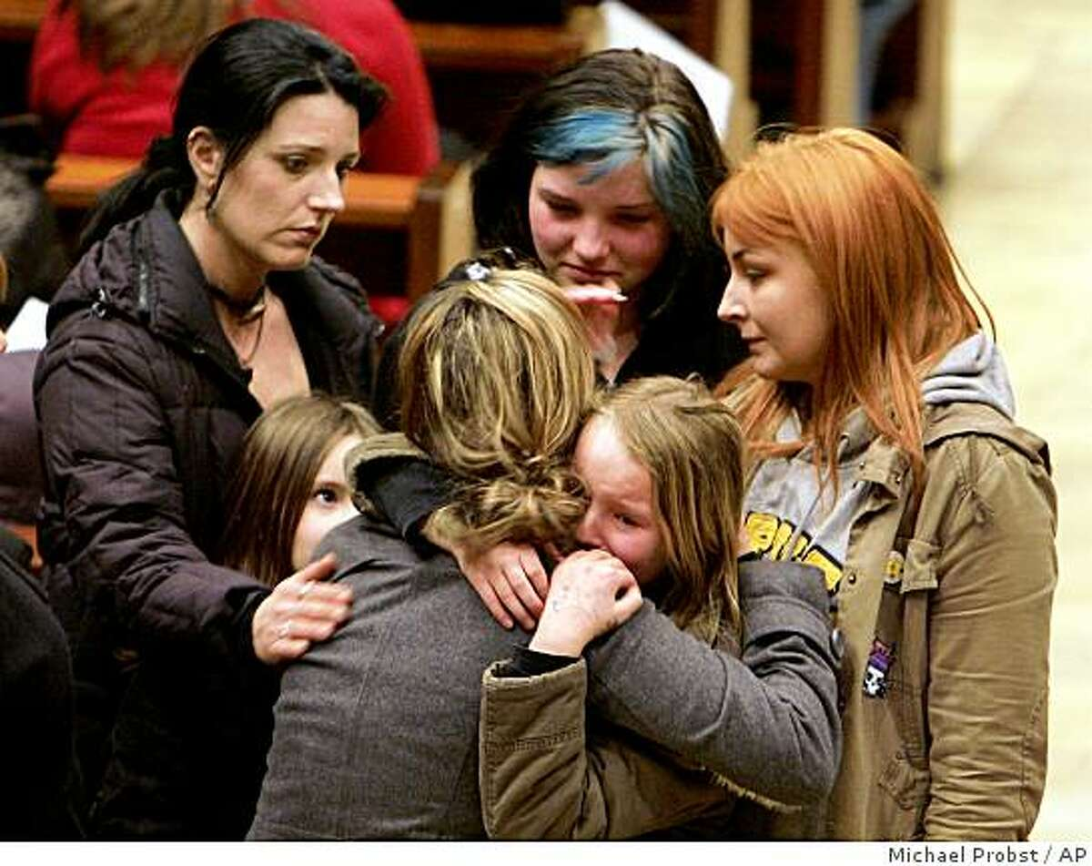People are seen while they embrace each other in tears in a church in Winnenden, Germany, Wednesday, March 11, 2009. A 17-year-old gunman dressed in black opened fire inside his former high school in southwestern Germany on Wednesday killing 15 people, 11 of them women and girls, before turning the gun on himself, authorities said. (AP Photo / Michael Probst)