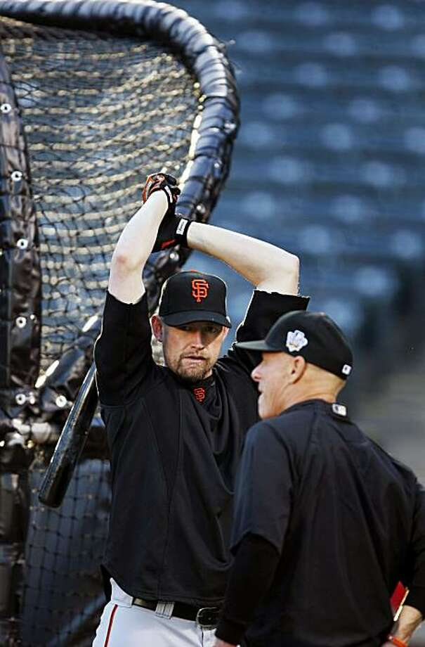 Giants Aubrey Huff talks with third base coach Tim Flannery as he warms up for batting practice at Rangers Ballpark in Arlington Friday Oct. 29, 2010 The Giant have a two game lead in the World Series with the Texas Rangers, with game three to be played Saturday night. Photo: Lance Iversen, The Chronicle