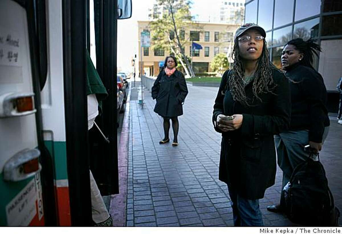 Candra Harvey, holding two crisp dollar bills, waits to board an AC Transit bus at 12th and Broadway on Monday March 9, 2009 in Oakland, Calif.