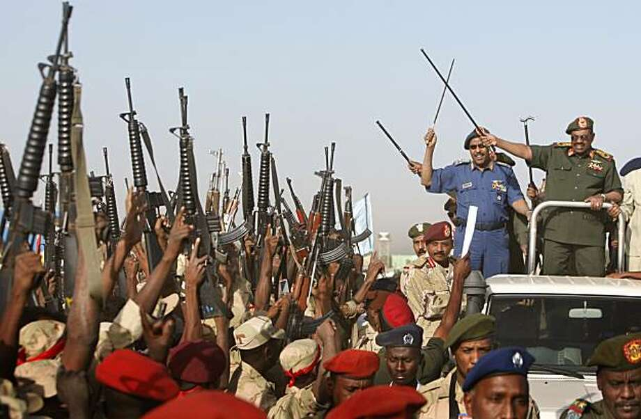 Sudanese President Omar al-Bashir, right, on top of a vehicle gestures to army soldiers during a pledge of allegiance rally for the military in Khartoum, Sudan, Monday, March 16, 2009.  Sudanese army, police and security units signed a pledge of allegiance to al-Bashir, vowing to defend him against the International Criminal Court arrest warrant issued last week. (AP Photo/Nasser Nasser) Photo: Nasser Nasser, AP