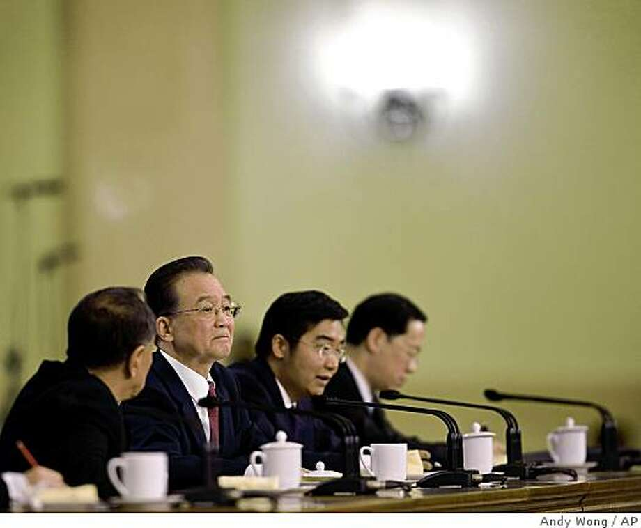 Chinese Premier Wen Jiabao, second from left, reacts during a news conference after the closing ceremony of the National People's Congress at the Great Hall of the People in Beijing Friday, March 13, 2009. Photo: Andy Wong, AP