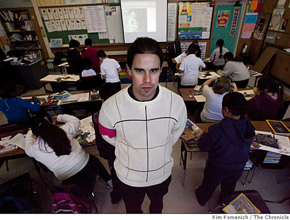 """Gabe Lucero teaches his third grade class at Rio Vista Elementary School in Bay Point, Calif., on Thursday, Mar. 12, 2009. Lucero is one of 26,000 California teachers to receive a layoff warning notice. He is wearing a pink armband to call attention to the """"pink slip"""" that might come his way."""