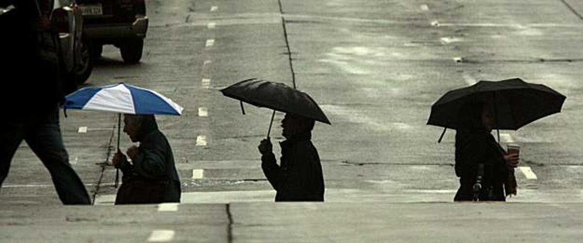 Pedestrians make their way across Pine Street in the rain under umbrellas in San Francisco, Calif. on Thursday, January 21, 2010.