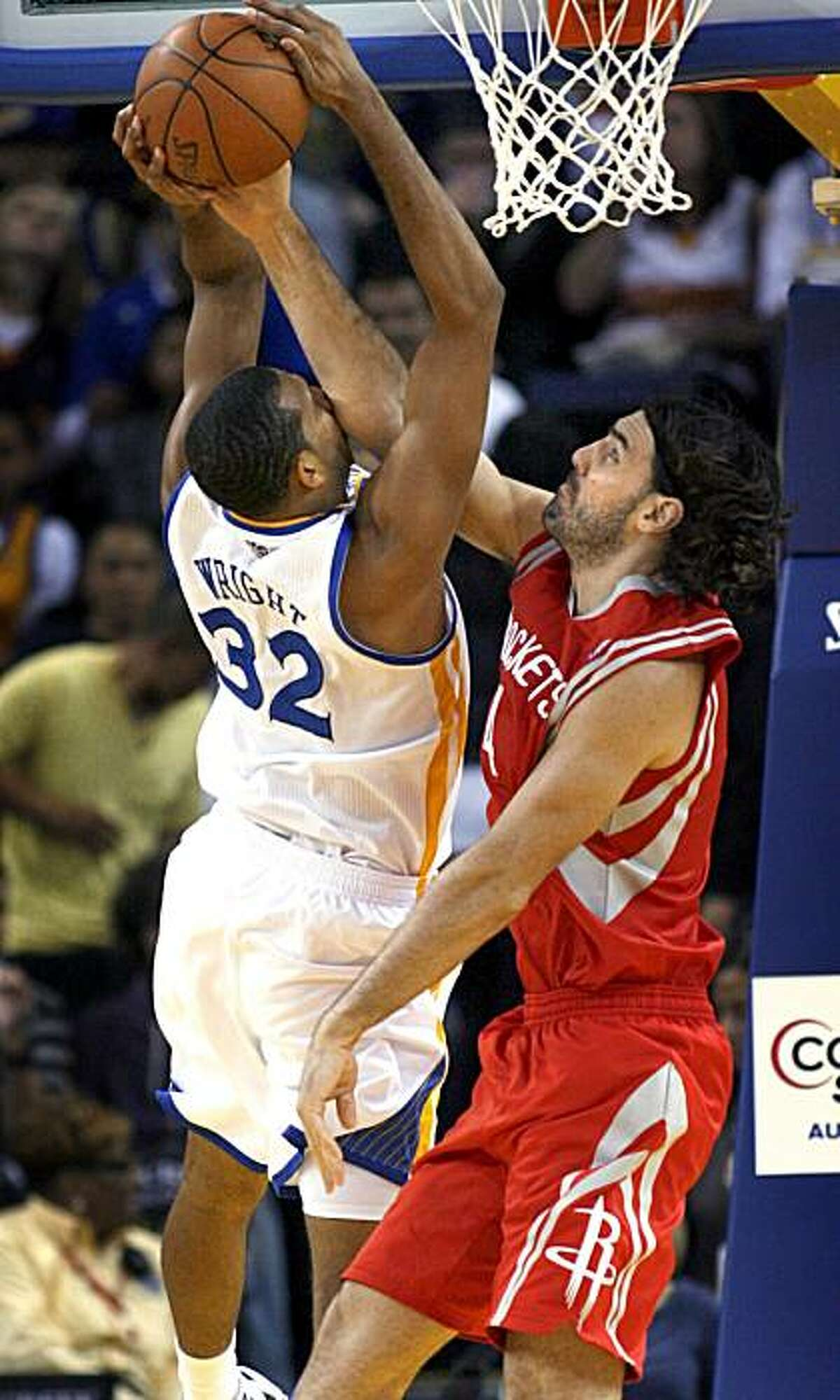 Golden State Warriors' Brandan Wright (32) takes an elbow to the face from Houston Rockets' Luis Scola, of Argentina, while shooting during the first half of an NBA basketball game Wednesday, Oct. 27, 2010, in Oakland, Calif.