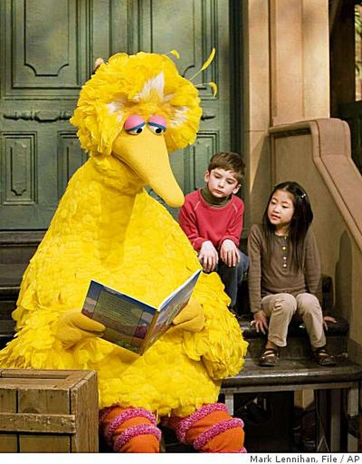 "Big Bird reads to Connor Scott and Tiffany Jiao during a taping of ""Sesame Street"" in New York in 2008. Photo: Mark Lennihan, File, AP"