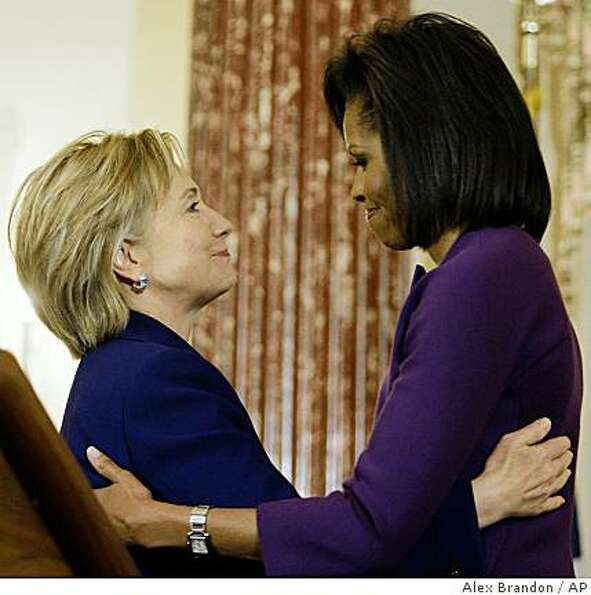 Secretary of State Hillary Rodham Clinton hugs first lady Michelle Obama at the International Women