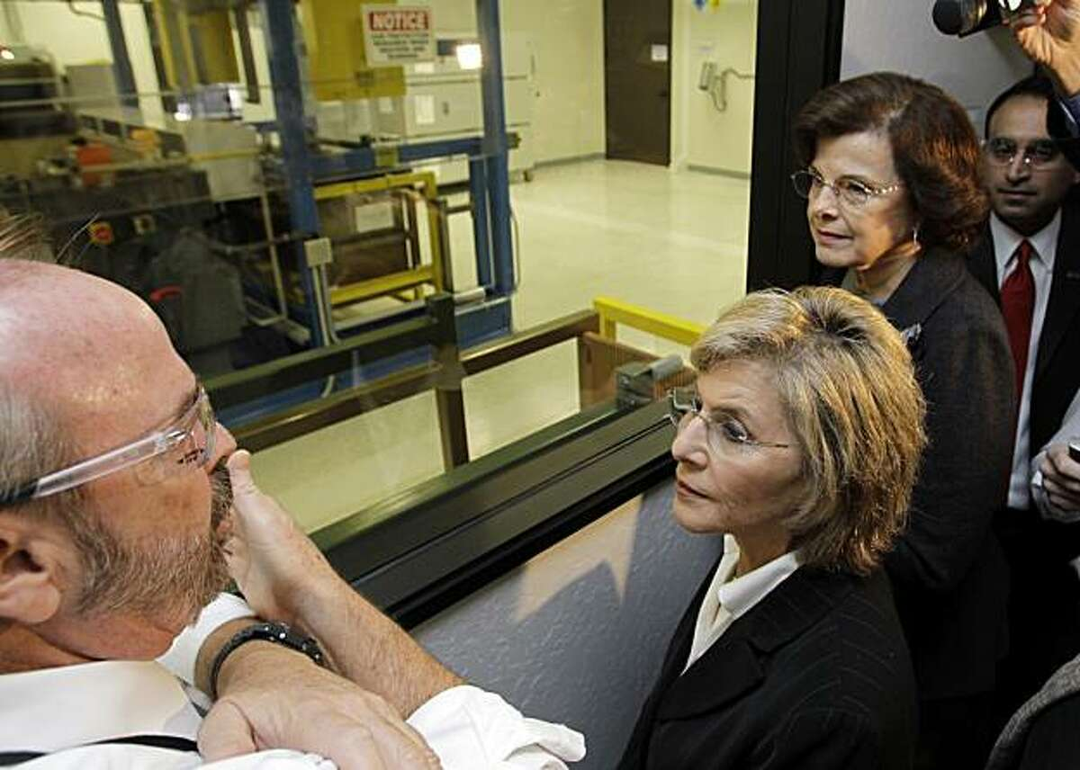 Sen. Barbara Boxer, (D-Calif.), center, who is running for reelection, and Sen. Dianne Feinstein, (D-Calif.), right, gets a tour by solar panel manufacturer Stion Corp. CEO Chet Farris, left, in San Jose, Calif., Monday, Oct. 25, 2010.