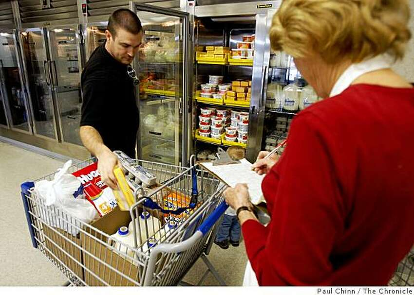 A store volunteer (right) helps Jon Isom select his groceries at the Bishop's Storehouse in Concord, Calif., on Wednesday, Feb. 25, 2009. Operated by the Latter-Day Saints, the storehouse provides food and provisions to church members in need.