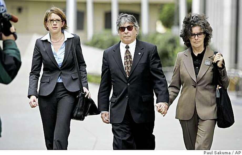 ** RETRANSMISSION TO CORRECT DATE ** Capt. John Cota, center, leaves a federal courthouse in San Francisco, Friday, March 6, 2009, with his wife, Teresa Barrett, right, and attorney Claudia Quiroz, left, after he plea guilty to misdemeanor charges. Cota was the pilot at the helm of the cargo ship Cosco Busan that caused a massive oil spill in the San Francisco in Nov. 2007. (AP Photo/Paul Sakuma) Photo: Paul Sakuma, AP