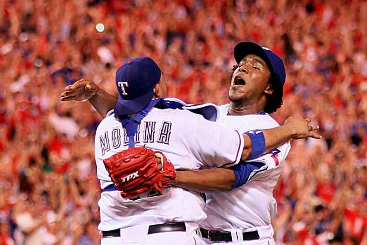 ARLINGTON, TX - OCTOBER 22: Bengie Molina #11 and Neftali Feliz #30 of the Texas Rangers celebrate after defeating the New York Yankees 6-1 in Game Six of the ALCS to advance to the World Series during the 2010 MLB Playoffs at Rangers Ballpark in Arlington on October 22, 2010 in Arlington, Texas.