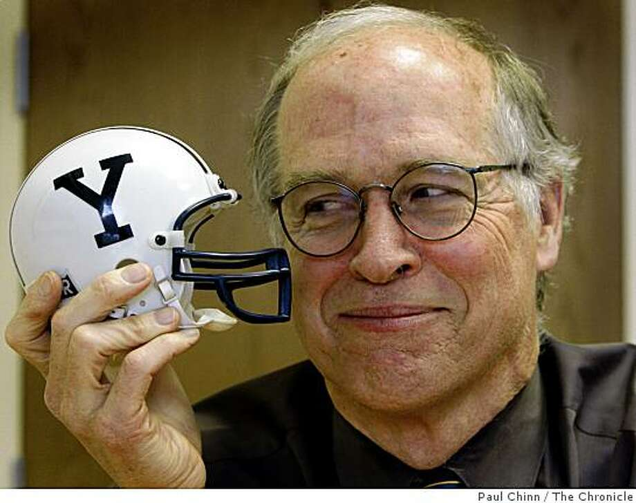 Andy Coe holds a miniature Yale football helmet in his office in Palo Alto, Calif., on Thursday, Feb. 26, 2009. Coe was a linebacker for Yale's football team in 1968 when the Bulldogs blew a 16-point lead over Harvard with only seconds left on the clock. Photo: Paul Chinn, The Chronicle