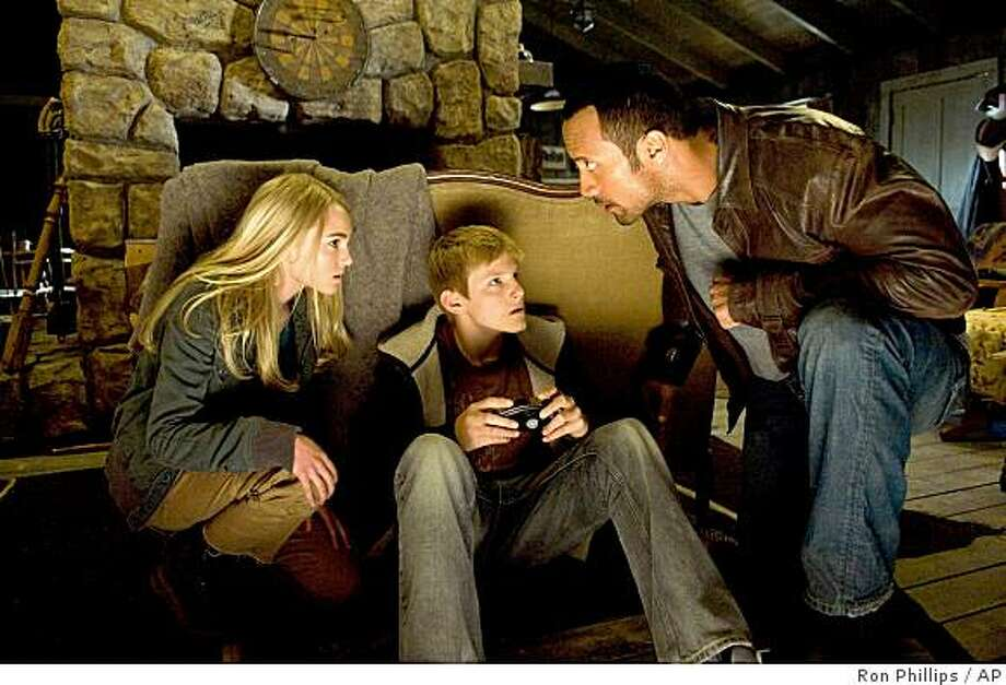 "In this film still released by Disney, actors, from left, AnnaSophia Robb, Alexander Ludwig and Dwayne Johnson are shown in a scene from ""Race to Witch Mountain."" Photo: Ron Phillips, AP"
