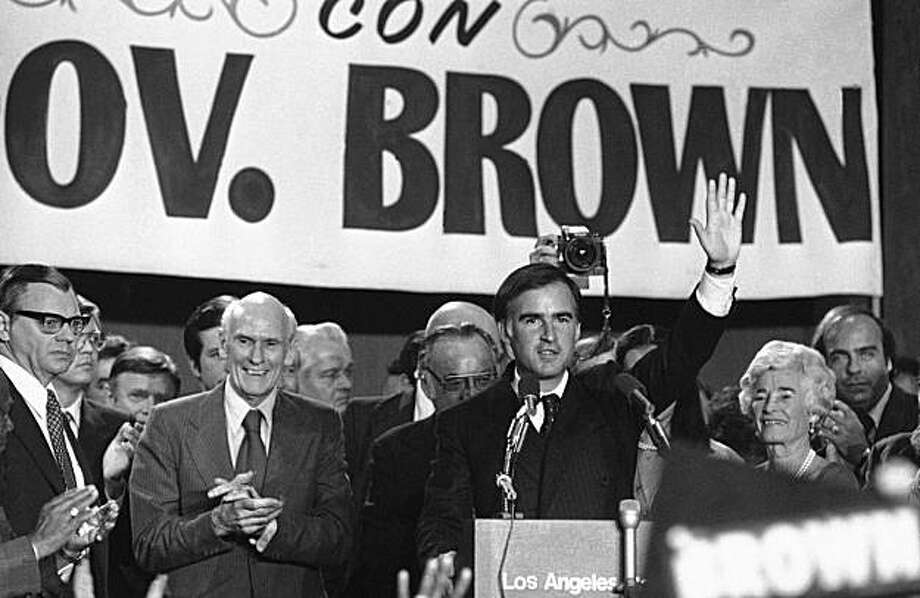 California Governor Jerry Brown Jr., with his parents, former Gov. and Mrs. Pat Brown in the background, waves to supporters in Los Angeles, Tuesday, Nov. 8, 1978 following his re-election. Brown is a Democrat. (AP Photo/McLendon) Photo: McLendon, ASSOCIATED PRESS