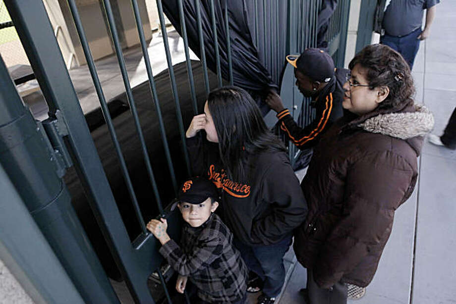 Giants fans, l-r, Jericko Gonzalez, 6, his mom, Elizabeth Gonzalez, Darryl Monroe, and Yasmina Gonzalez, (Elizabeth's mother-in-law) watch the Giants practice through pulled-back curtains from the right field viewing area. The San Francisco Giants held their first team practice at AT&T Park in San Francisco, Calif., on Monday, October 25, 2010, following their NLCS win over the weekend. The team is now preparing for the World Series which opens at AT&T Park on Wednesday. Photo: Carlos Avila Gonzalez, The Chronicle