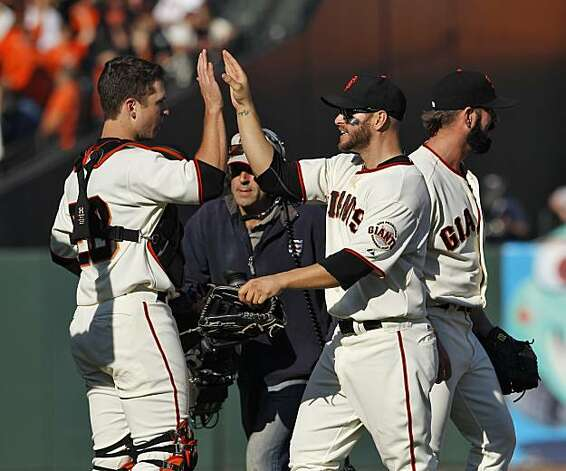 Cody Ross high fives Buster Posey as the Giants celebrated their win on the field. The San Francisco Giants played the Philadelphia Phillies at AT&T Park in San Francisco, Calif., on Tuesday, October 19, 2010, in Game 3 of the National League Championship Series. The Giants defeated the Phillies 3-0. Photo: Carlos Avila Gonzalez, The Chronicle