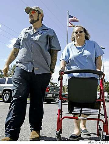 Bonnie Bigger, 60 (right)  and her son Jason, 29, walk to their car after attending a foreclosure workshop in Fort Pierce, Fla., on Friday. Their lender began foreclosure proceedings against them for falling $4,500 behind on their $776-a-month mortgage payments on a condo they have been living in since 1984. Photo: Alan Diaz, AP