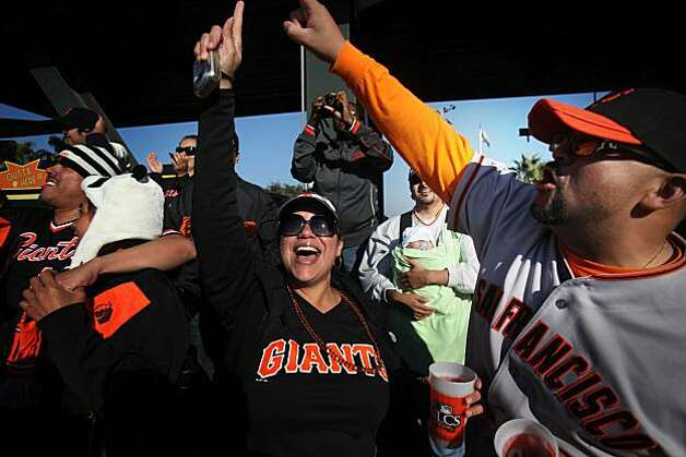 With a Giants victory confirmed, Lucy Castillo (ctr) and her husband Victor Castillo (rt), of Hayward throw their hands in the air after the final out of game 3 of the National League Champion series with the San Francisco Giants and the Philadelphia Phillies on Tuesday Nov. 19, 2010 in San Francisco, Calif.  Giants won with a final score of 3-0. Photo: Mike Kepka, The Chronicle
