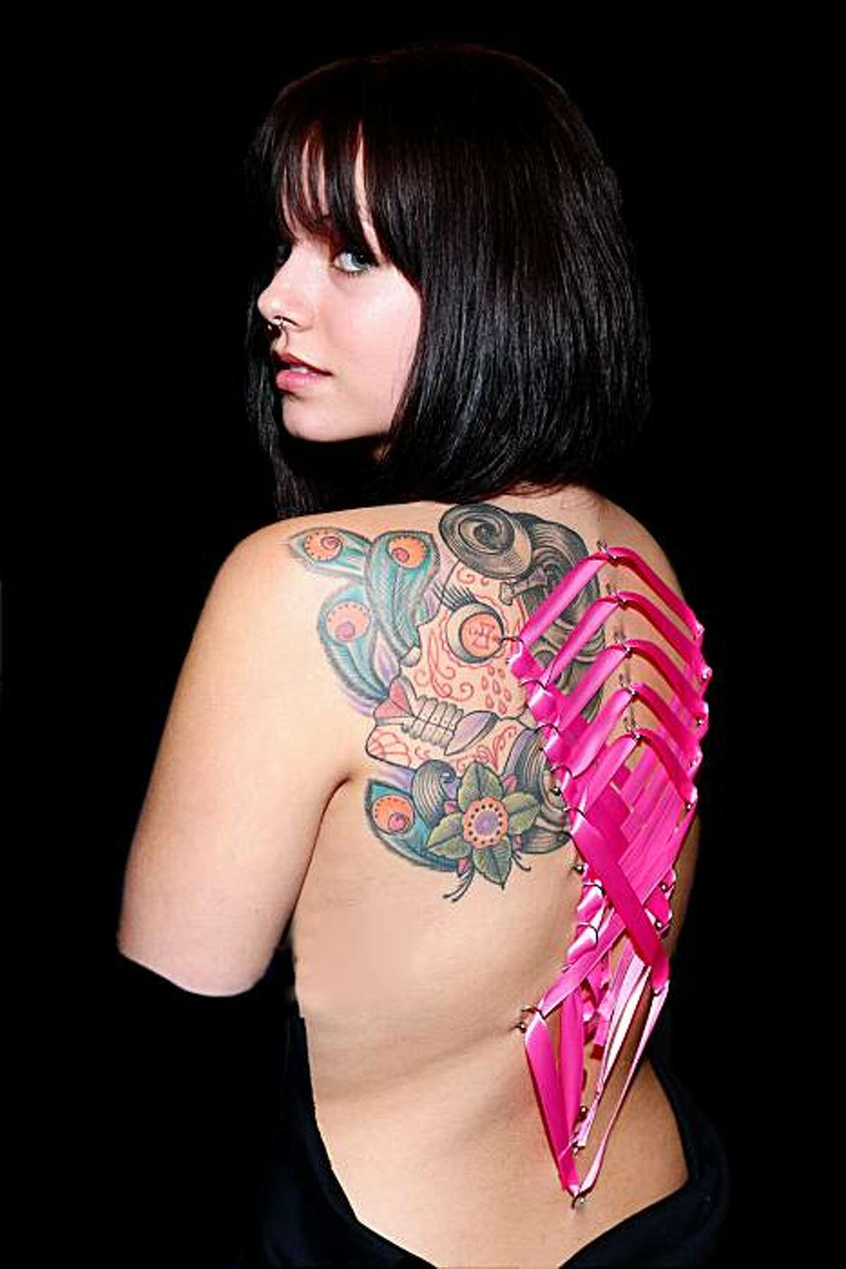 Monique Millier of San Jose models a corset piercing at the Body Art Expo in San Francisco and August. It is the second time she has had her back pierced and laced.