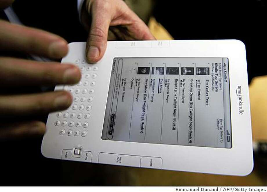 People test a Kindle 2 after a press conference unveiling latest version of Amazon's popular electronic reader, the Kindle, in New York, February, 9, 2009. The Kindle 2 adds a feature which reads a book aloud, is thinner, faster, crisper, with longer battery life, and capable of holding hundreds more books, Bezos said. The Kindle 2 costs 359 USD, available from amazon.com. and the first units will be shipped February 24. AFP PHOTO/Emmanuel Dunand (Photo credit should read EMMANUEL DUNAND/AFP/Getty Images) Photo: Emmanuel Dunand, AFP/Getty Images