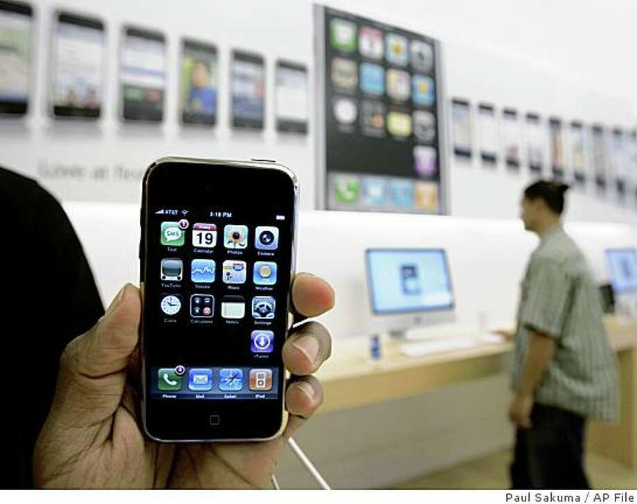 ** FILE ** In this Oct. 19, 2007 file photo, a customer holds an Apple iPhone at the Apple store in Palo Alto, Calif., Friday, Oct. 19, 2007. Following the success of Apple Inc.'s iPhone, mobile phone manufacturers are racing to produce touch screen models of their own. (AP Photo/Paul Sakuma, file) Photo: Paul Sakuma, AP File