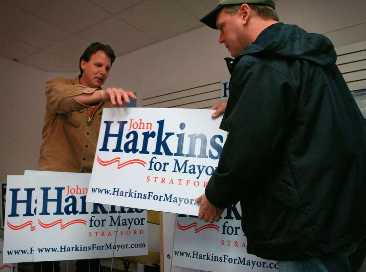 Rick Vanicky, left of Stratford, helps new mayor-elect John Harkins pack up lawn signs at Stratford Republican headquarters on Wednesday.