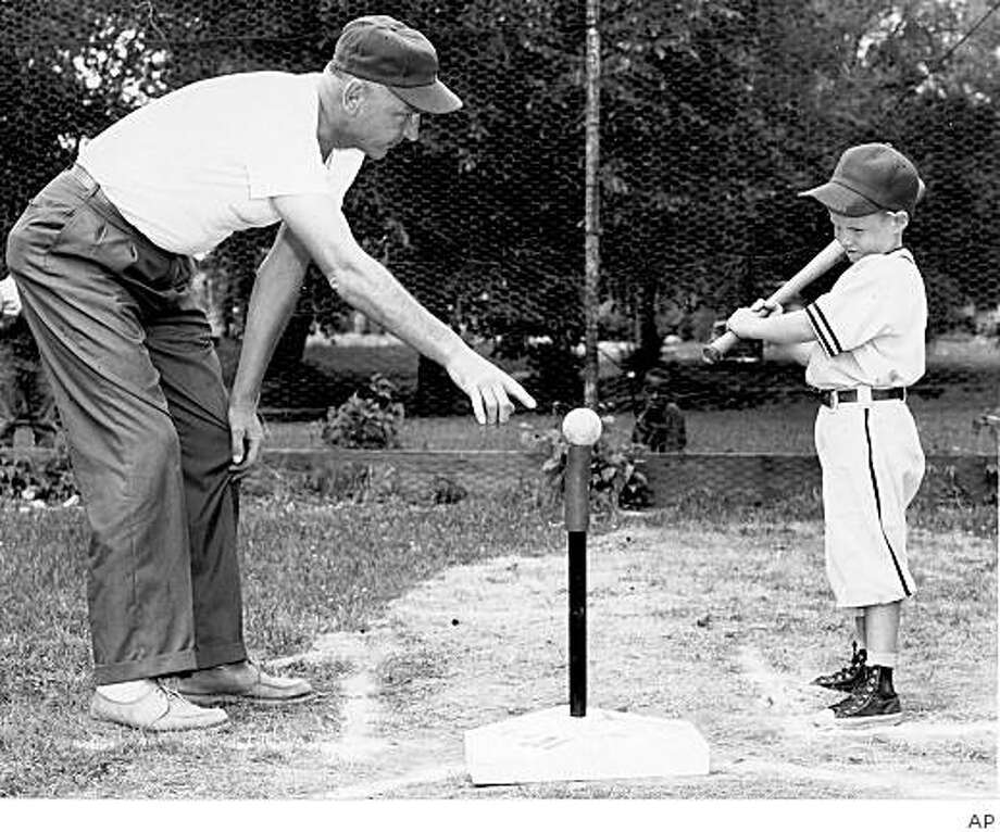 In a photo provided by Albion, Mich., historian Frank Passic, Jerry Sacharski, left, gives instructions to 5-year-old Craig LeClair in 1958. The Michigan man known for helping to popularize T-ball as an organized youth sport has died. The J. Kevin Tidd Funeral Home in Albion says Sacharski, 93, died Friday, Feb. 27, 2009, at his home in Albion. The game's exact origin is unclear but behind Sacharski, Albion in 1956 became one of the nation's first communities in which T-ball was played as an organized sport. (AP Photo/Frank Passic via Battle Creek Enquirer) ** NO SALES ** Photo: AP