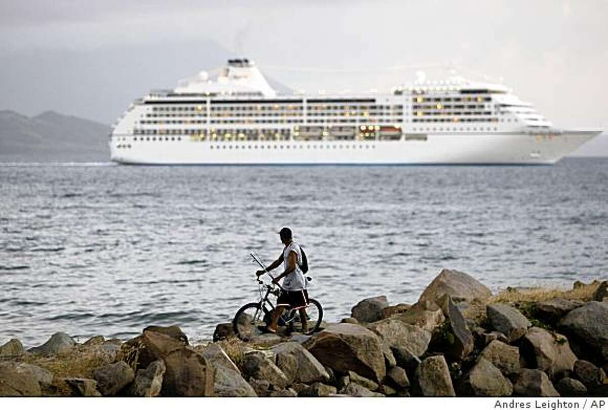 **APN ADVANCE FOR SUNDAY MARCH 1** A fisherman looks at a cruise ship departing from the Basseterre port in the Caribbean island of St. Kitts, Thursday, Jan. 22, 2009. Three miles from shore, the cruise ships that flock to the Caribbean cross a boundary where the sea becomes a dump for metal, glass and other waste that is flushed overboard. The islands need only give a U.N. maritime agency approval to outlaw the pollution, but it comes with a catch: Some of the tiny countries are hesitating out of fear they will be forced to take ashore mountains of trash. (AP Photo/Andres Leighton)