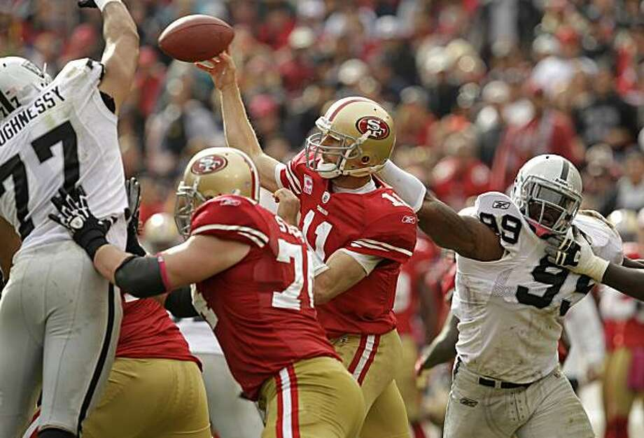 San Francisco 49ers quarterback Alex Smith (11) passes while pressured by Oakland Raiders defensive end Matt Shaughnessy (77) and defensive end Lamarr Houston (99) in the third quarter of an NFL football game in San Francisco, Sunday, Oct. 17, 2010. Photo: Marcio Jose Sanchez, AP