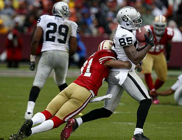 William James of the 49ers catches the Raiders' Darrius Heyward-Bey after a short gain in the first half Sunday at Candlestick Park. Photo: Brant Ward, The Chronicle