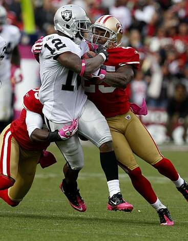 Raiders receiver Jacoby Ford is dragged down by two 49ers defenders in the fourth quarter Sunday at Candlestick Park Photo: Brant Ward, The Chronicle