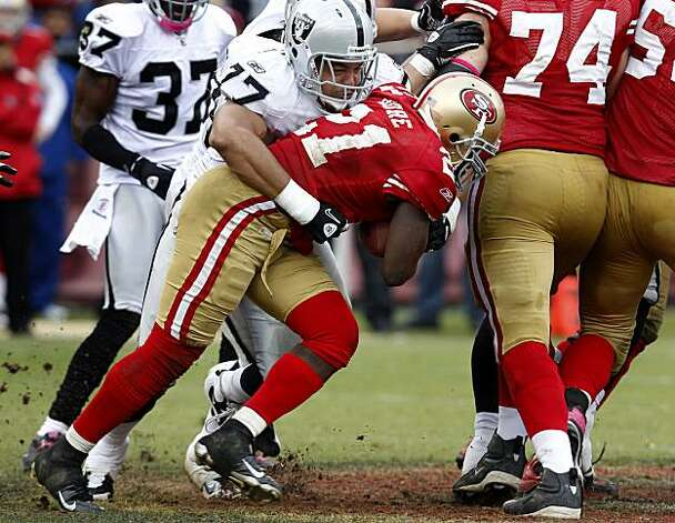 The 49ers' Frank Gore gets a gain before Matt Shaughnessy drags him down in the second half Sunday at Candlestick Park. Photo: Brant Ward, The Chronicle